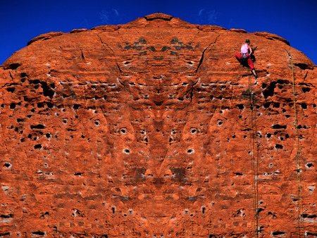 Rock climbing on red sandstone for sport recreation challenge and fun Stock Photo