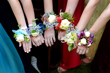 Girls holding arms out with corsage flowers for prom