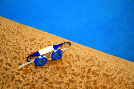 Swimming goggles next to pool with blue clear water