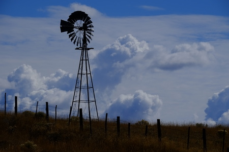 Windmill on hillside in countryside rural America with sky and clouds 스톡 콘텐츠