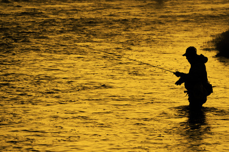 Silhouette of Fishing Flyfishing rod reel in river with golden sunlight Stock Photo
