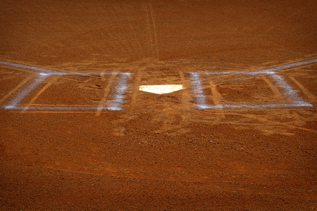 Baseball homeplate with batter box chalk lines in brown clay dirt Stock Photo