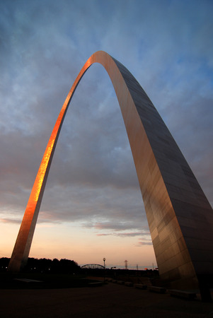 St Louis Arch landmark metal gateway sunset glowing orange Stock Photo