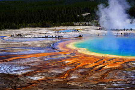 Grand Prismatice Spring in Yellowstone National Park with tourists viewing the spectacular natural scene Stock Photo
