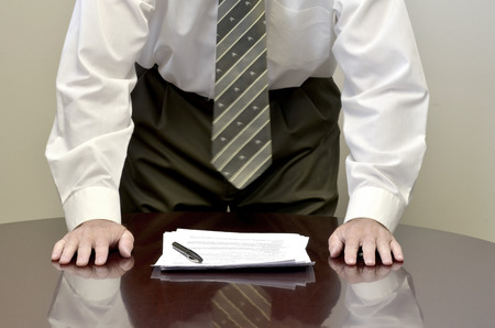Man standing at desk signing contract papers documents businessman or  lawyer 写真素材