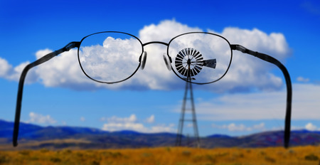 Windmill on hillside in countryside rural America with sky and clouds glasses for clear vision