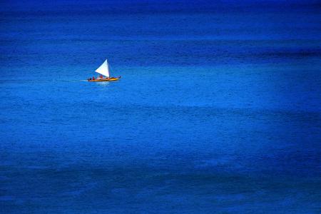 Sailboat sailing on calm blue ocean water