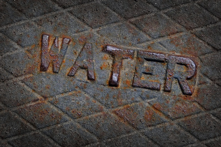 Water sign on metal cover of rusted manhole Stock Photo