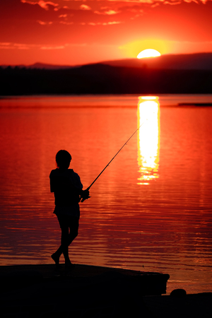 Young child or kid fishing in lake or river at sunset recreation fun