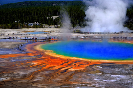 Grand Prismatice Spring in Yellowstone National Park with tourists viewing the spectacular natural scene 写真素材