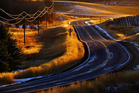 Old country road with turns and curves telephone wires glowing in golden sunlight Фото со стока