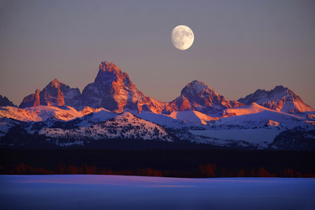 Sunset light with alpen glow on Tetons Teton mountains rugged with moon rising