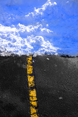 Road in the winter with yellow line leading to snow and ice dangerous roadway
