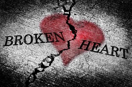 Large crack in cement with words broken heart and red texture emotions hurt feelings