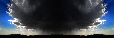 Amazing symmetrical thunderstorm over mountains horizon with blue sky
