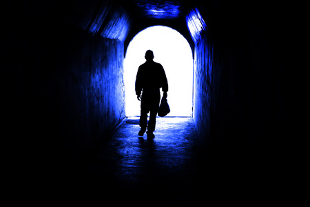 Person walking through a tunnel towards light at end. Accomplishing goal or leaving darkness. Imagens
