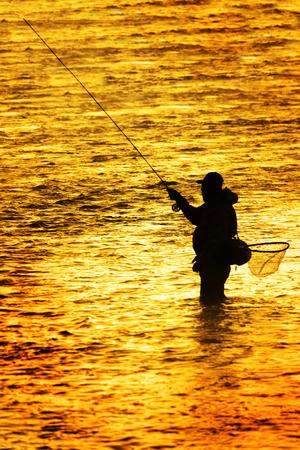 Silhouette de pêche à la mouche moulinet de canne à pêche en rivière avec la lumière du soleil dorée qui l'entoure pêcheur tôt le matin
