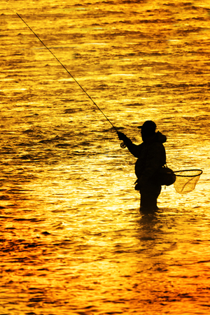 Silhouette of Fishing Flyfishing rod reel in river with golden sunlight surrounding him early morning fisherman