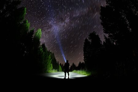 Man standing in dark with stars with flashlight forest night sky