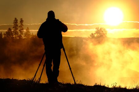 Photographer with tripod and camera taking photographs of sunrise or sunset with steam and trees