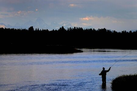 Flyfisherman fly fisherman fishing on river with Tetons in Background Banco de Imagens