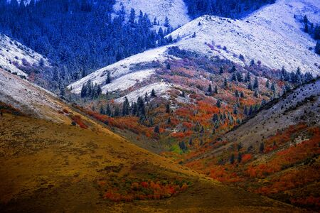 Mountain landscape in late fall with autumn tree colors and first snow