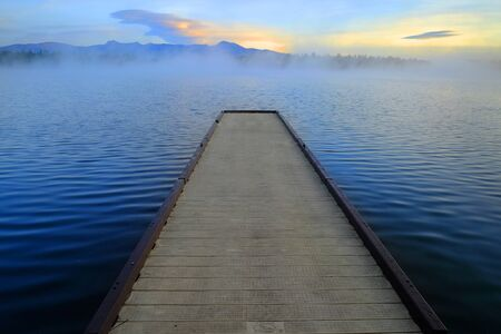 Dock floating on lake with early morning mist
