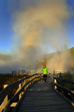 Woman walking on boardwalk above and around steam rising from a spring in Yellowstone National Park Banco de Imagens