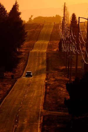 Cars driving on old country road at sunset of sunrise power lines