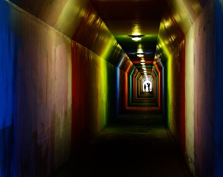 Person silhouetted silhouette walking through colorful tunnel towards achievement Banco de Imagens