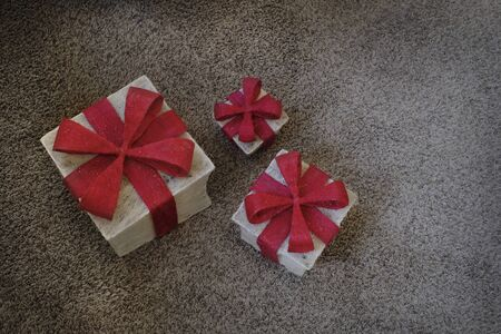Gifts with red bows on carpet in home for the holidays or a birthday celebrations