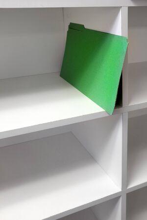Green file folder on shelf for business organization symbolizing getting started
