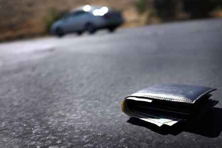 Wallet fallen out of car on roadway road Фото со стока