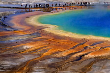Grand Prismatice Spring in Yellowstone National Park with tourists viewing the spectacular natural scene Banco de Imagens