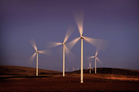 Windmill wind turbines spinning fast in wind at sunset or sunrise  Banco de Imagens