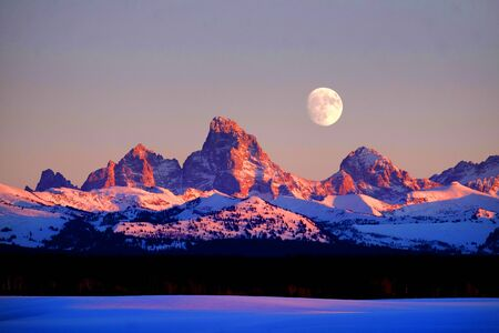 Sunset light with alpen glow on Tetons Tetons mountains rugged with moon rising Banco de Imagens