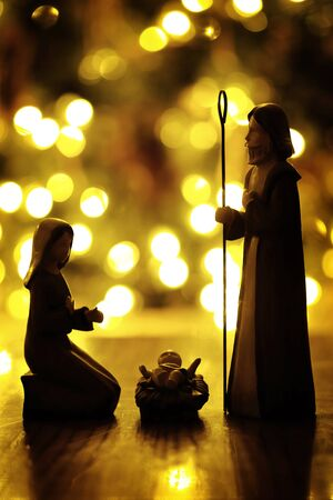Closeup of Nativity with Christmas lights out of focus for the true meaning of Christian Holiday