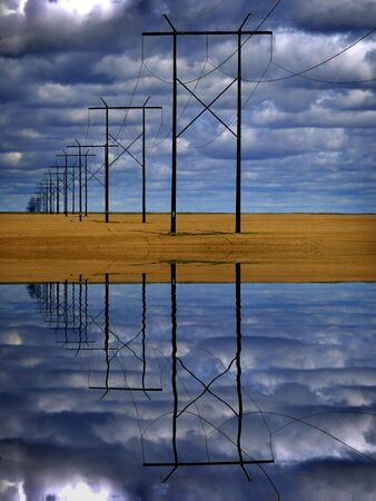 Powerlines in field with blue sky and clouds representing utility reflection in water Banque d'images