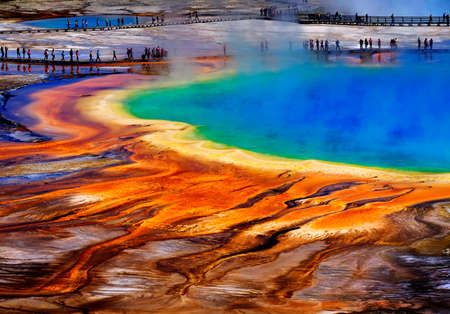 Grand Prismatic Spring in Yellowstone National Park with tourists viewing the spectacular natural scene