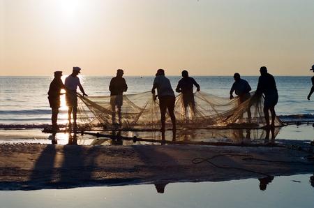 fish net: old fishermen on the beach Stock Photo