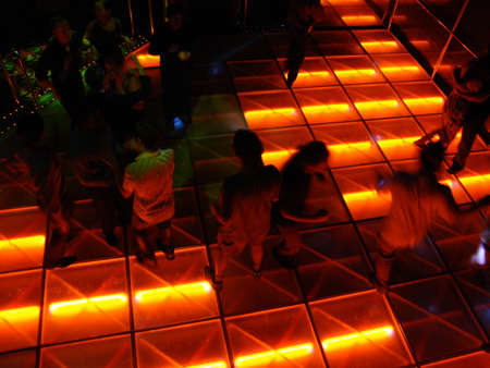 Disco Style Dance Hall with a group of people dancing on one side and a couple dancing on the other.  Cool patterned lighting on the dance floor.