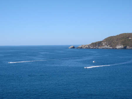 Two Jet skis race by a boat in Zihuatanejo bay on a clear day in Mexico