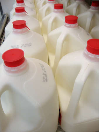 expiration: lined up in a row Milk Jugs are displayed at a SuperMarket                                Stock Photo