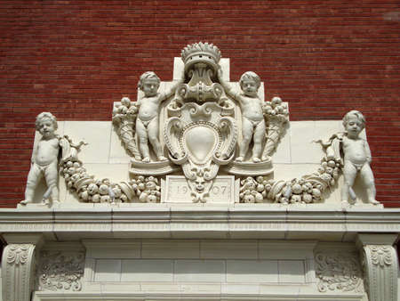 Matte-glazed Terra Cotta cherubs holding garlands above a plaque that reads 1907, the date of the original buildings completion which was the landmark Jessie Street Power Substation, designed by Willis Polk in 1907.  The details are located above one of t