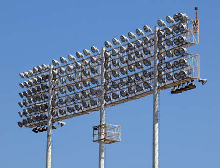 Stadium-style lights, taken at Oakland Colisuem looking forward, clear blue sky background, during the daytime so the lights are off.