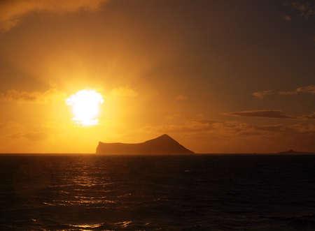 Sunrise over small island off the Oahu coast in Hawaii