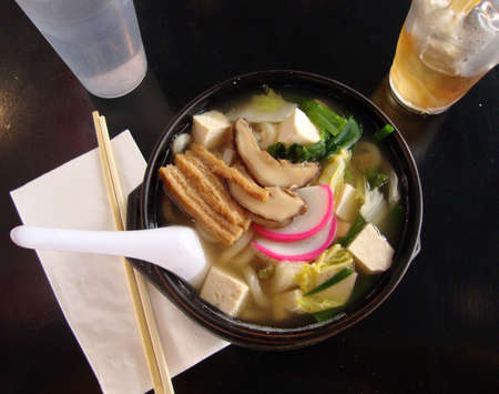 tofu udon soup with chopsticks, drinks, and many yummy vegetables served fresh