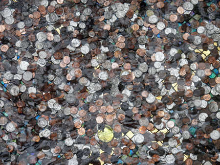 Large collection of USA and other coins underwater in a pond for good luck photo