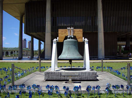 Freedom bell and blue pinwheels in front of the Hawaii State Capitol                                Stock Photo