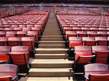 bleachers: Rows of empty orange stadium seats going upward. Candlestick stadium San Francisco